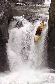 a photo of a kayak going over a river falls